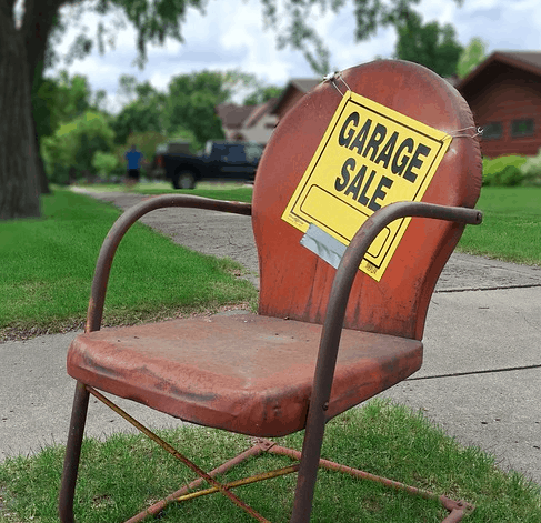 A chair in front of a garage sale.