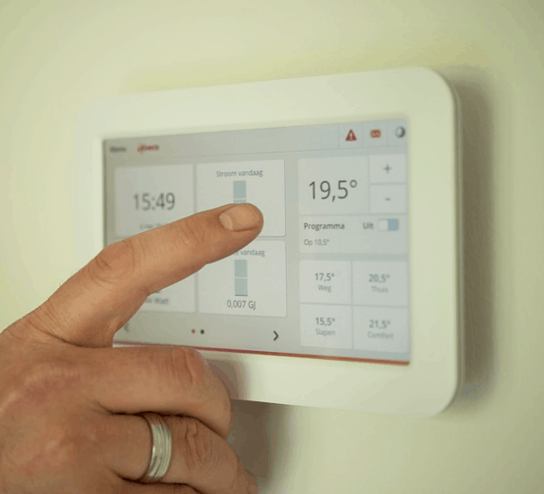 Adjusting the thermostat on a home HVAC system.