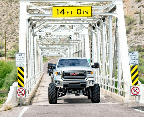 A truck with a lift kit on it going over a bridge.