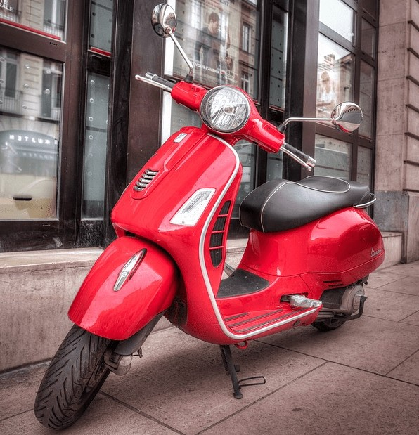 A moped on a sidewalk purchased with a bad credit loan.