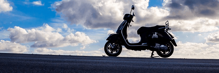 A picture of a moped against a sky background.