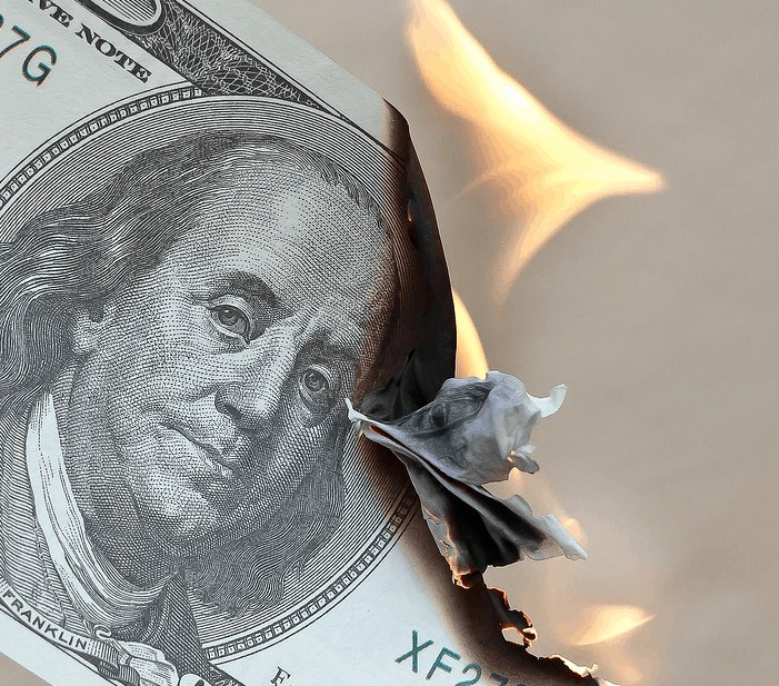 An image of burning money being wasted.
