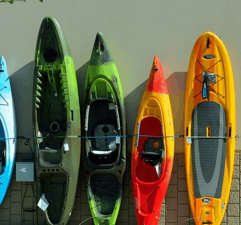 A bunch of kayaks along the wall.