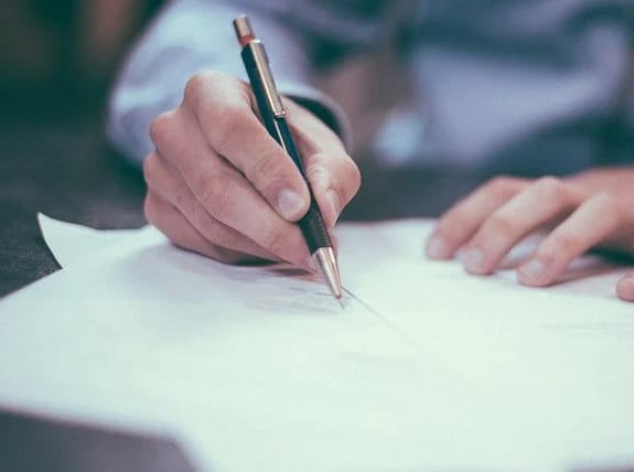 A man signing an auto loan document.