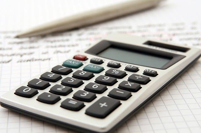 A calculator being used to add up savings.