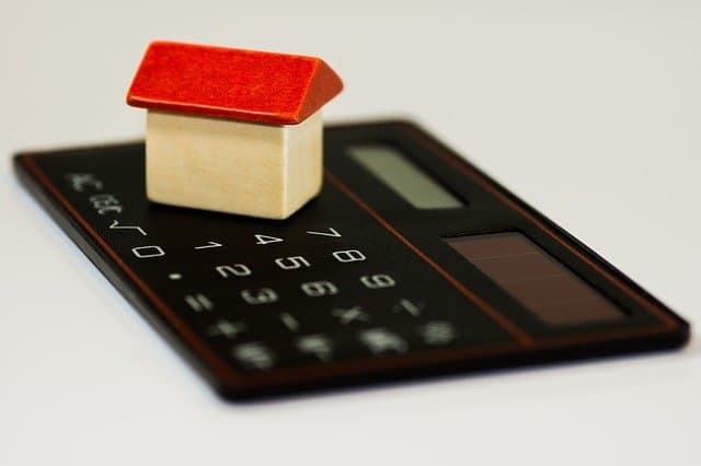 A toy home on a calculator used to calculagte a mortgage.