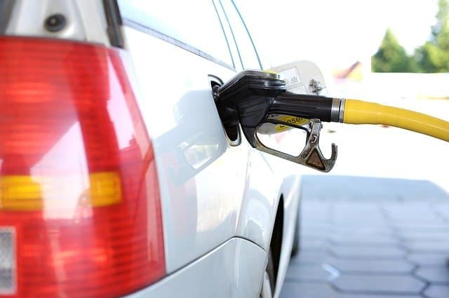 A person gassing up, adding to their vehicle operation costs.