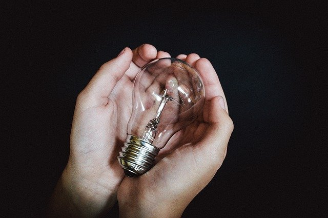 A person holding a lightbulb in their hand, symbolizing an invention they have no money for.